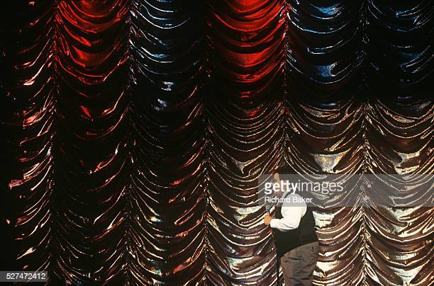 A comic entertainer with glitzy backdrop performs a standup routine on stage during cruise ship voyage Surrounded by the showbiz styled curtain we...