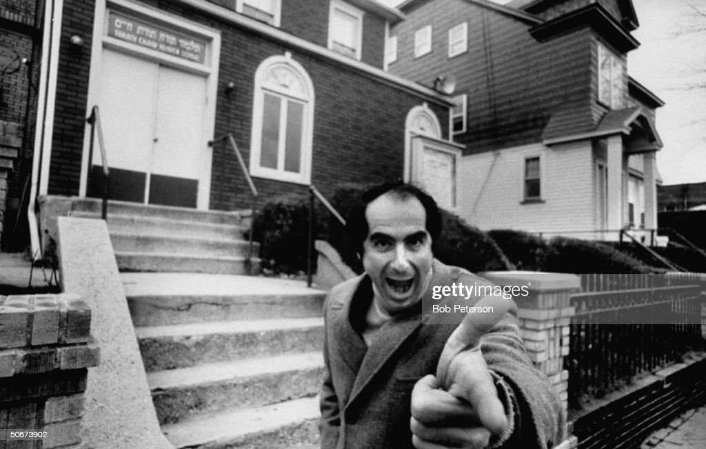 Comic face made by author, Philip Roth, while standing near Jewish center and Hebrew school he probably attended as a boy.