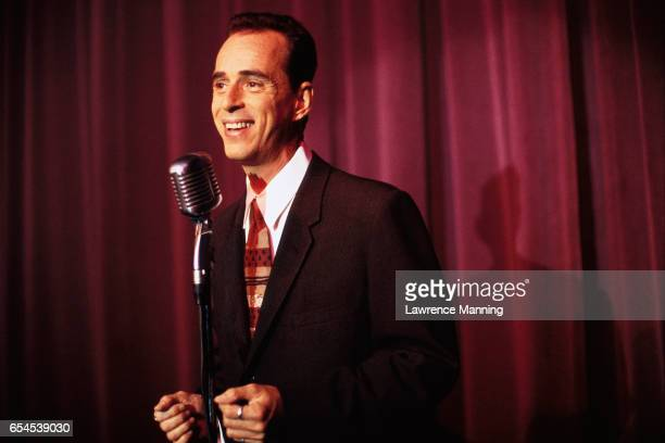 comic standing at microphone - stand up comedian stock pictures, royalty-free photos & images