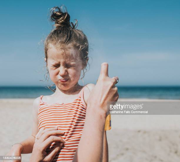 comical image of little girl holding her breath and wincing as sun cream is applied to her face - headwear stock pictures, royalty-free photos & images