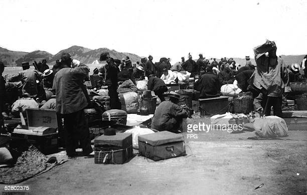 A group of primarily Chinese and East Asian immigrants waits on a wharf after disinfection at Angel Island San Francisco Bay California 1910s The...