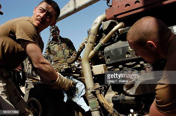 Command Group Troopers SSG Jeff Marjerrison of Wiedfield CO and PFC Reed Monson of Boise ID struggle to remove an oil hose from the engine of their...