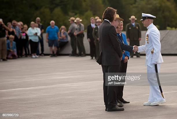 Command Senior Chief Ryan King of the US Navy Ceremony Guard presents a flag to Gordon Felt while Secretary of the Interior Sally Jewell looks on the...