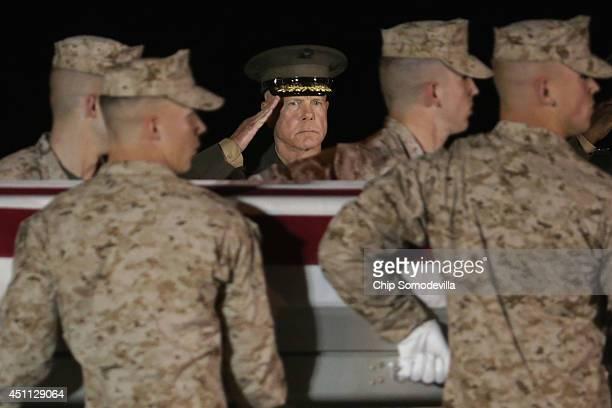 Commandant of the Marine Corps Gen. James Amos salutes as a U.S. Marine Corps carry team transfers the remains of Staff Sgt. David Stewart at Dover...