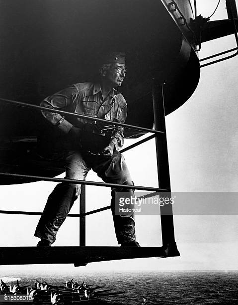 Commander Edward Steichen stands on a platform overlooking the deck of the USS Lexington Propellor airplanes are on the deck