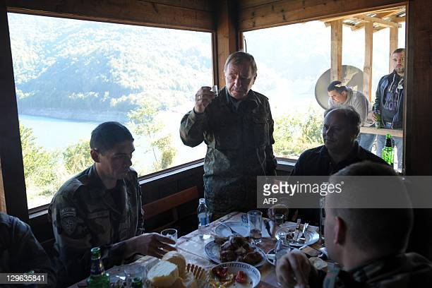 Commander Erhard Drews makes a toast with rakia during a meeting with local Kosovo Serbs at the closed SerbiaKosovo border crossing of Brnjak in...