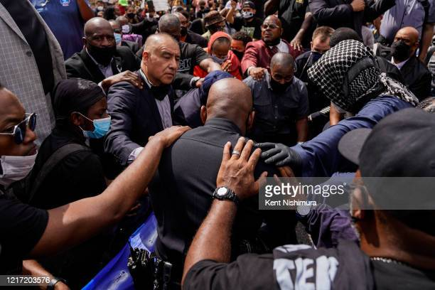 Commander Gerald Woodyard takes a knee with clergy members from the Los Angeles area as they participate in a march in downtown Los Angeles to LA...
