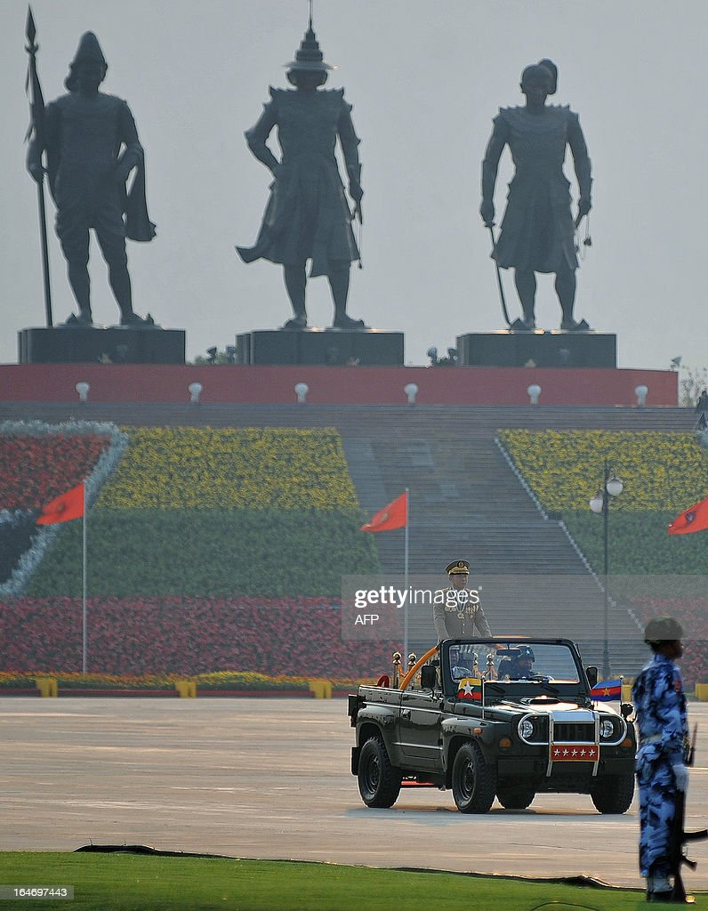 Commander in Chief Min Aung Hlaing stands in a car as he reviews troops during a ceremony marking Myanmar's 68th Armed Forces Day at a parade ground in Naypyidaw on March 27, 2013. Opposition leader Aung San Suu Kyi attended Myanmar's Armed Forces Day for the first time. AFP PHOTO / Ye Aung THU