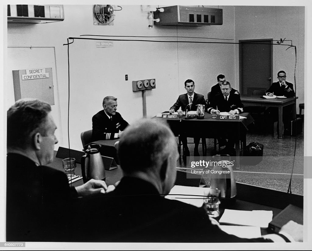 Commander Lloyd E. Bucher (left, back to the wall), commanding officer of the USS Pueblo, a Navy ship captured by North Korea in the Sea of Japan in 1968, answers questions during a naval court of inquiry. January 24, 1969. His counsel, E. Miles Harvey and Captain James E. Keyes, sit at a nearby table (right).