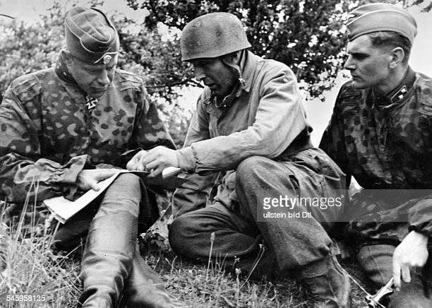 WORLD WAR II JUNE 1944 A commander of a German paratrooper unit goes over plans with SS Brigadier General Werner von Ostendorf near the town of...