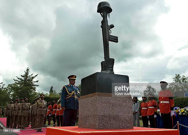Commander of Kenya's Defence Forces Gen Julius Karangi [C] observes a moment of silence on October 14 2012 in front of a monument unveilled at the...