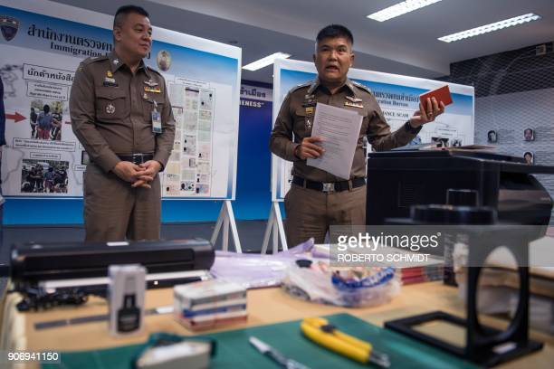 Commander of the Immigration Bureau Lt Gen Suttipong Vongpint holds a fake Singaporean passport during a press conference in Bangkok on January 19...