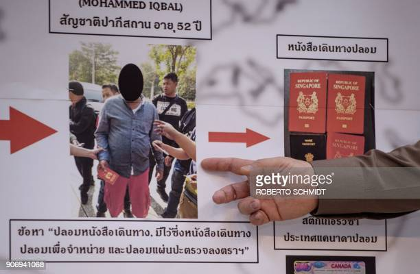 Commander of the Immigration Bureau Lt Gen Suttipong Vongpint points to a board with information about an apprehended passport forger during a press...