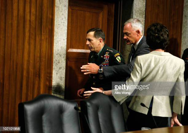 Commander of the United States Central Command Army Gen David Petraeus is escorted away after he briefly collapsed while testifying during a hearing...