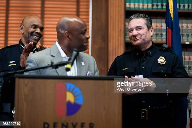 Commander Paul Pazen smiles as he is ribbed by Mayor Michael B Hancock while chief Robert White looks on as Pazen is introduced as Denver's new chief...
