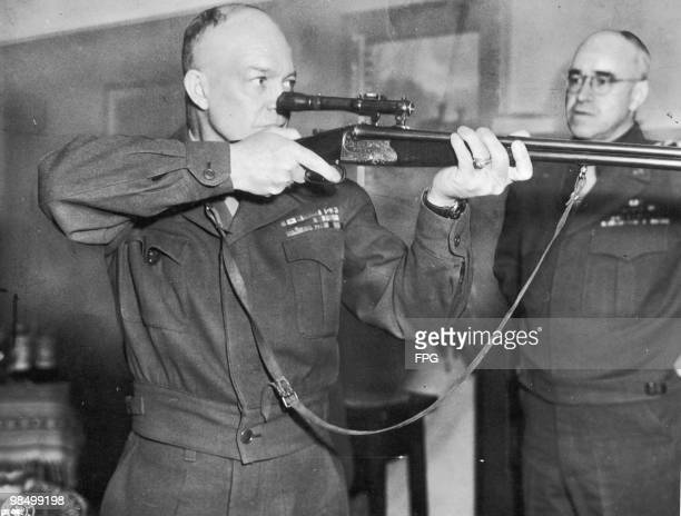 Commanding General of U.S. Army Europe, Dwight D. Eisenhower firing a German-made combination rifle-shotgun with telescopic sight, during a tour of...