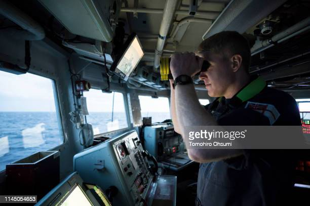 Commanding Officer Conor O'Neill works inside the bridge of British Royal Navy's HMS Montrose frigate during a joint exercise with Japanese Maritime...