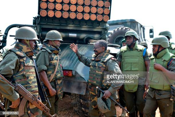 A commanding officer speaks with soldiers of the Armed Forces of the Democratic Republic of the Congo standing near a mobile multiple rocket launcher...