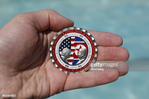A commemorative coin released by the White House for a potential peace summit featuring the names and silhouettes of US President Donald Trump and...