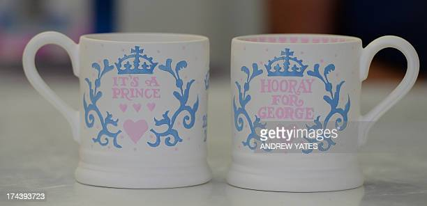 Commemorative mugs made to mark the birth of George Alexander Louis of Cambridge to Prince William and Catherine The Duchess of Cambridge stand on...