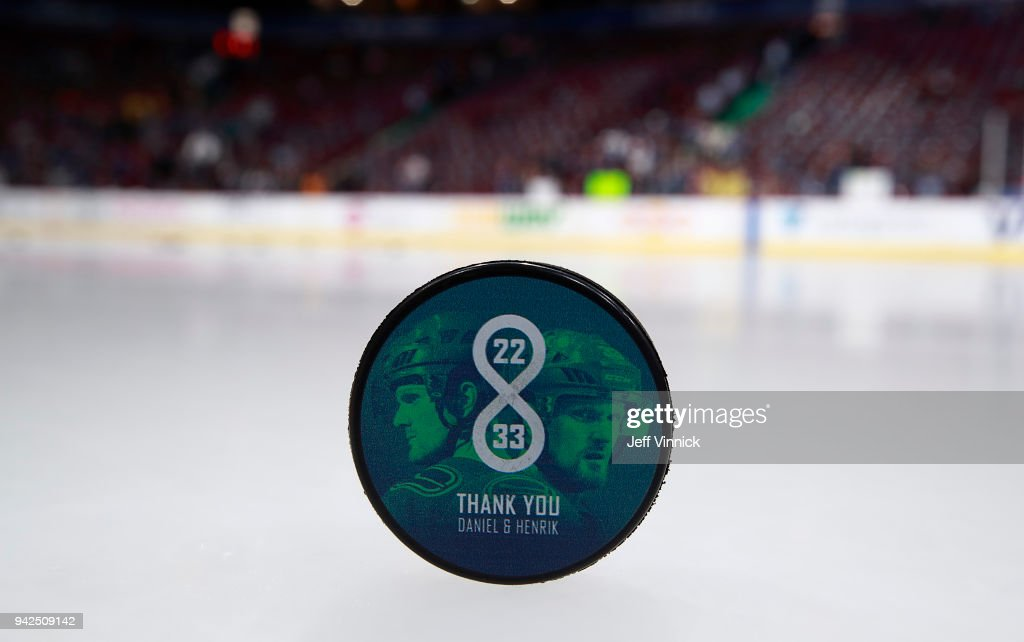 A commemorative puck shows Daniel Sedin #22 and Henrik Sedin #33 of the Vancouver Canucks before their NHL game against the Arizona Coyotes at Rogers Arena April 5, 2018 in Vancouver, British Columbia, Canada.