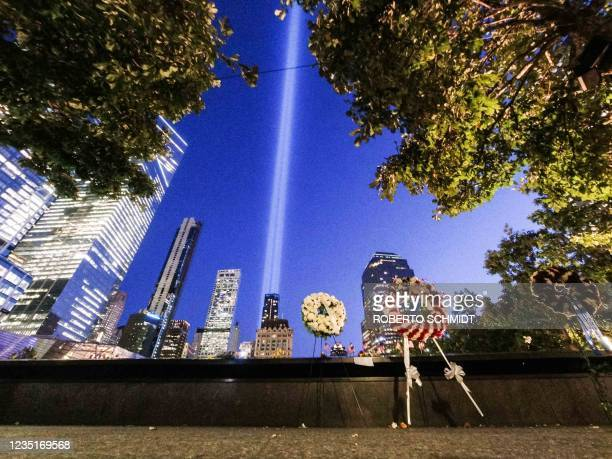 Commemorative wreaths are left at the 9/11 Memorial & Museum as the annual Tribute in Light projects two pillars of light into the night sky in New...