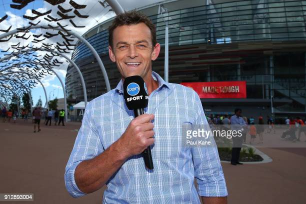 Commentator and former player Adam Gilchrist poses while doing a cross before the Big Bash League Semi Final match between the Perth Scorchers and...