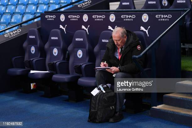 Commentator Martin Tyler takes notes as he sits on the team bench prior to the Premier League match between Manchester City and Manchester United at...