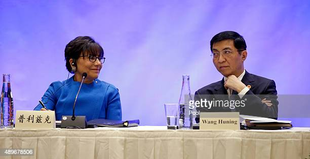 S Commerce Secretary Penny Pritzker left and Wang Huning member of the Politburo of the Communist Party of China listen as Chinese President Xi...