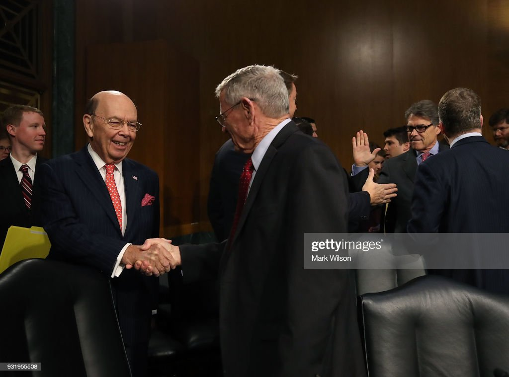 Commerce Secretary Wilbur Ross, (L), and Energy Secretary Rick Perry, (R), are greeted as they appear before the Senate Commerce, Science and Transportation Committee, on March 14, 2018 in Washington, DC. The committee is hearing testimony on President Donald Trump's plan to rebuld the nations infrastructure.