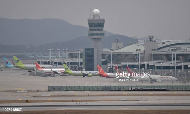 Commercial aircraft are seen parked on the tarmac at Incheon international airport, west of Seoul, on March 17, 2020. - Airlines have cancelled so...