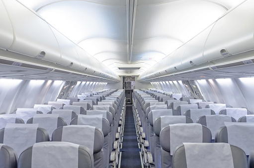 Commercial aircraft cabin with rows of seats down the aisle. 938439760