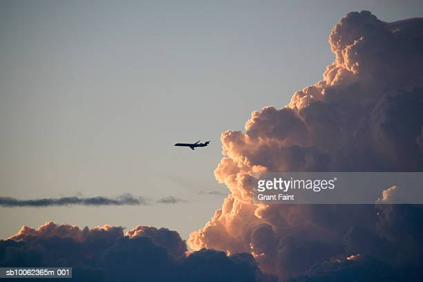 Commercial aircraft flying by large clouds