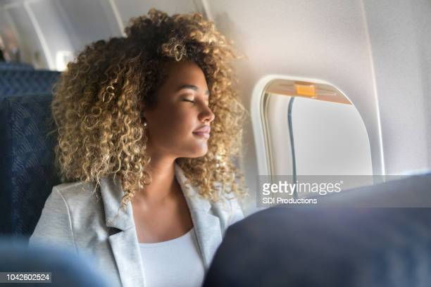 commercial airline passenger sleeps in window seat - serene people stock pictures, royalty-free photos & images