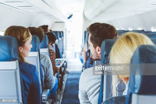 commercial airliner cabin with people travelling - izusek imagens e fotografias de stock