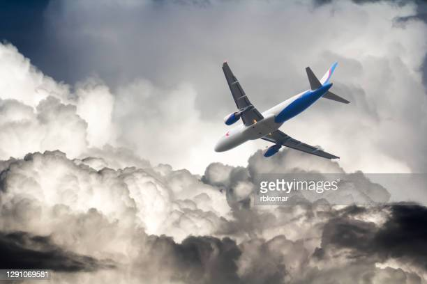 a commercial airplane flies through storm clouds - airplane crash stock pictures, royalty-free photos & images