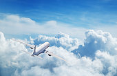 Commercial airplane flying above clouds