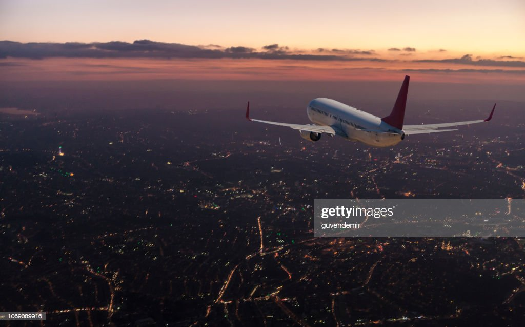Commercial airplane flying over big city at dusk : Stock Photo