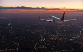 Commercial airplane flying over big city at dusk