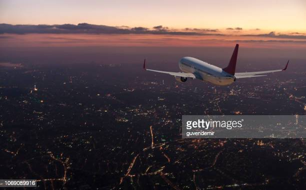 commercial airplane flying over big city at dusk - aeroplane stock photos and pictures