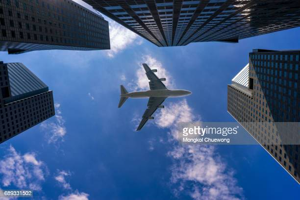 Commercial airplane flying over modern building