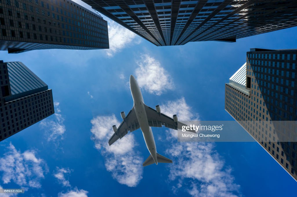 Commercial airplane flying over modern building : Stock Photo