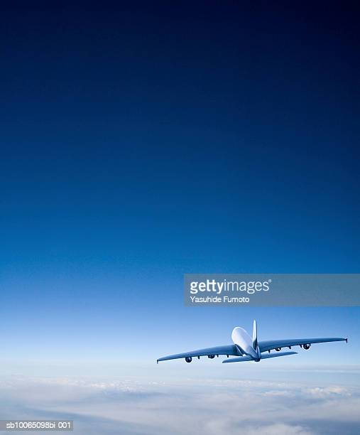 commercial airplane in flight, rear view - flying stock photos and pictures