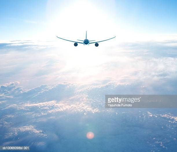 Commercial airplane in flight, rear view (lens flare)