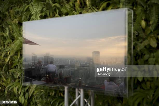 Commercial and residential buildings are reflected in a screen at a rooftop bar in Singapore on Wednesday June 13 2018 Tourism as well as the...