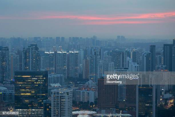 Commercial and residential buildings stand at dusk in Singapore on Wednesday June 13 2018 Tourism as well as the consumer sector will likely see a...
