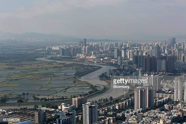 Commercial and residential buildings stand in the Luohu district right across from farmland on the Hong Kong side of the border in Shenzhen China on...