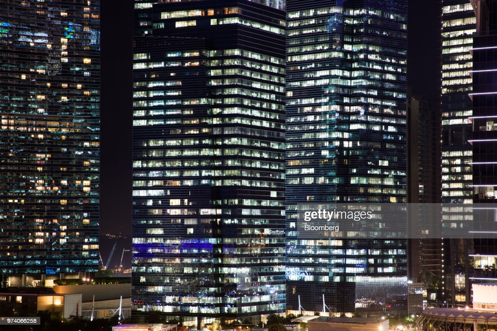 Commercial buildings in the central business district are illuminated at night in Singapore, on Wednesday, June 13, 2018. Tourism as well as the consumer sector will likely see a lift thanks to the influx of international media at the recent DPRK-USA Summit, according to RHB Research Institute Singapore Pte. Photographer: SeongJoon Cho/Bloomberg via Getty Images