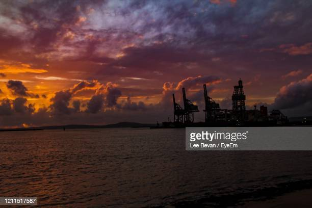 commercial dock by sea against sky during sunset - port talbot stock pictures, royalty-free photos & images