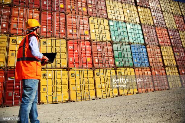commercial docks worker examining containers - heavy industry stock photos and pictures